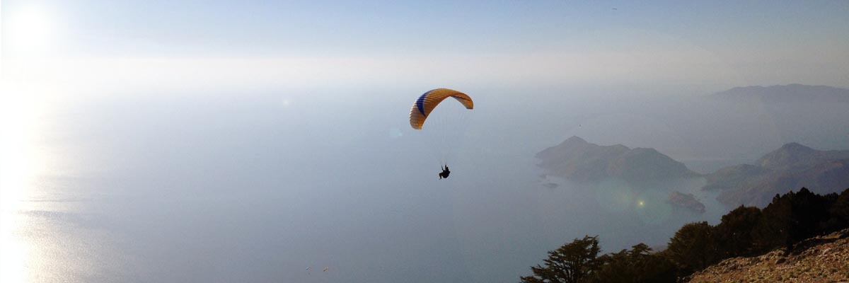 Early morning at the top of Babadag,Olu Deniz, Turkey, looking at Paraglider flying over sea.