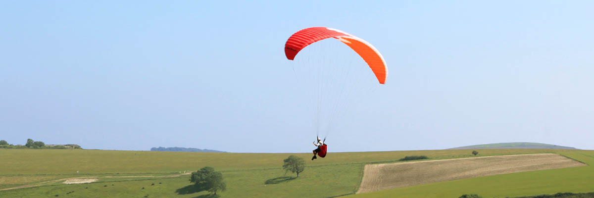 Red paraglider flying at Steyning